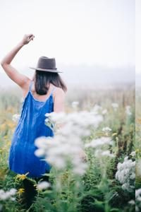 Frau von hinten in Blumenwiese winkend